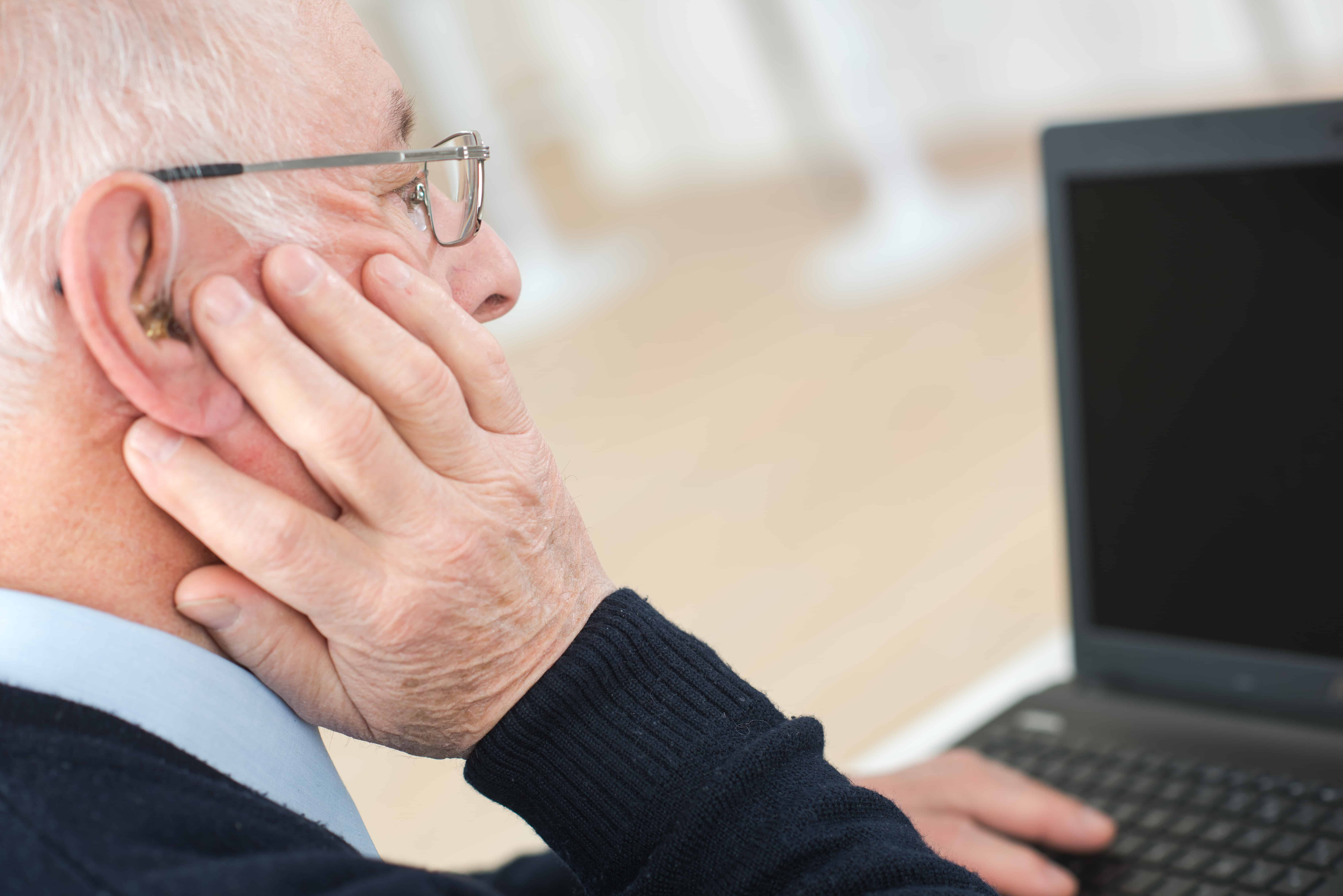 senior man suffering from deafness with computer